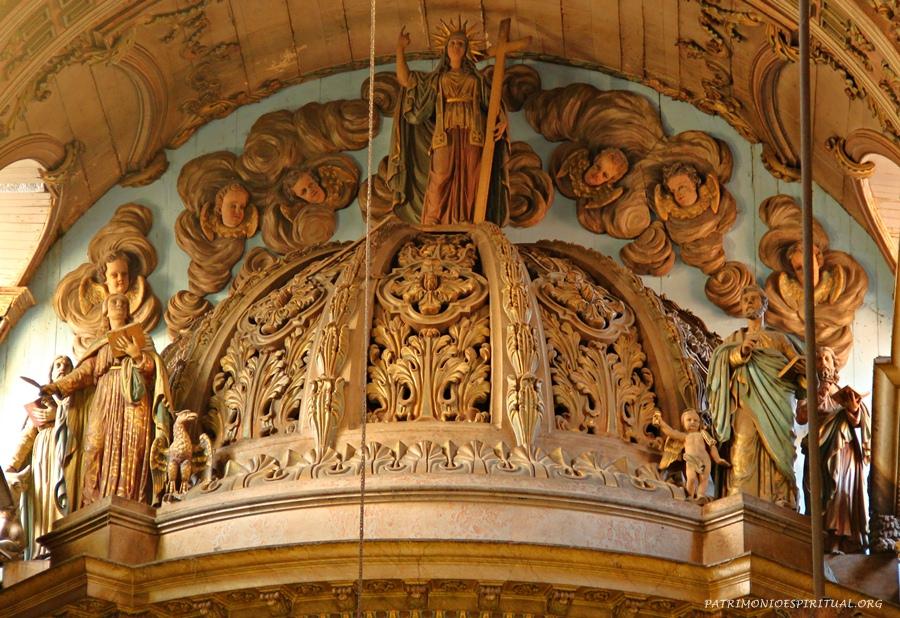Coroamento do baldaquino do altar-mor. Nele pode-se ver imagens dos quatro evangelistas, e no alto uma figura feminina representando a Igreja Católica.