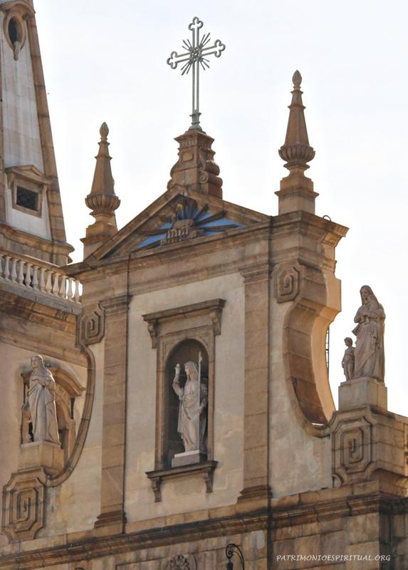Frontão da igreja, contendo a cruz, o símbolo do Cordeiro (Apocalipse cap. 5) sobre o livro de sete selos (dentro do triângulo azul), e as três virtudes teologais: a Esperança (esquerda), a Fé (centro), e a Caridade (direita)