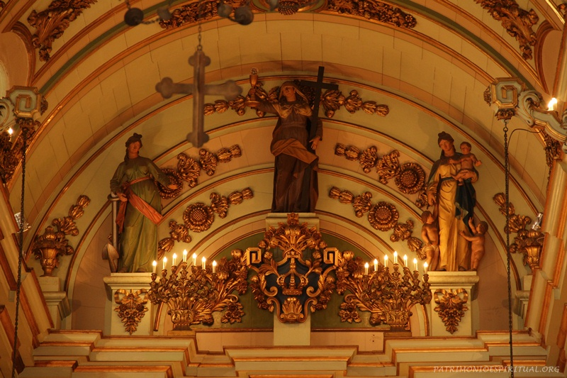 No alto do altar-mor, imagens figurativas representando as três virtudes teologais: a Esperança (esquerda), a Fé (no centro), e a Caridade (direita)