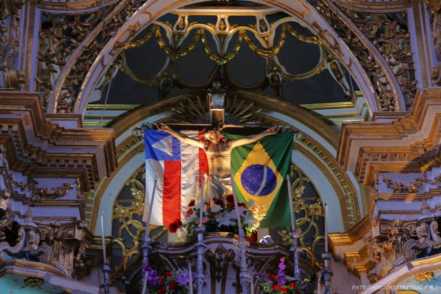 Crucifixo do altar mor, entre as bandeiras da Bahia e do Brasil.