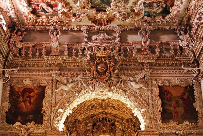 Arco cruzeiro, com o brasão da irmandade. À esquerda, quadro representando a ressurreição de Cristo, e à direita o seu batismo no Rio Jordão, pelas mãos de São João Batista.